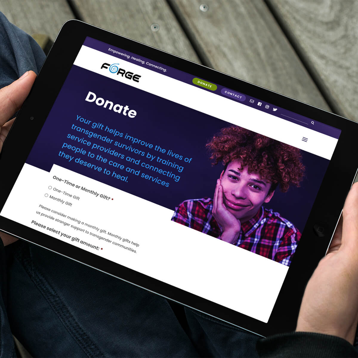 Hands holding tablet showing FORGE website donate page